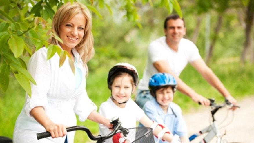 Cheerful family riding bicycles.