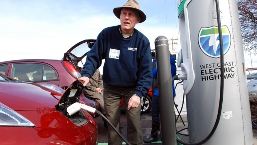 Bruce Sargent of Ashland, Ore., tops off the charge on his Nissan Leaf on Friday, March 16, 2011 at a new electric car charging station in Central Point, Ore.