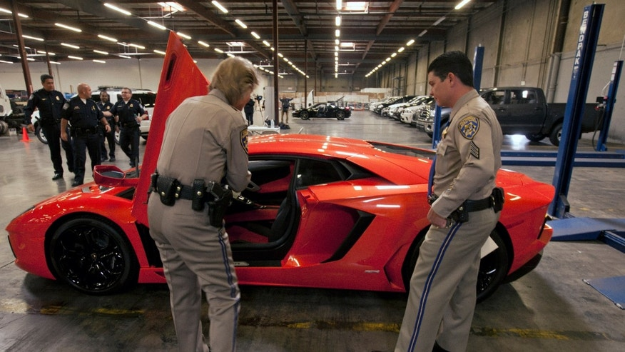 "California Highway Patrol officers: Lt. Glenda Brents, left, and Sgt. Mike Stefanoff, check the vin number of an intercepted 2012 Lamborghini Aventador LP700-4 ""supercar,"" that was being illegally exported with a lesser declared value, being held by U.S. Customs and Border Protection, next to other 20 high-end stolen vehicles that were intercepted on their way to Honk Kong and Vietnam, in Carson, Calif., on Tuesday, April 3, 2012. (AP Photo/Damian Dovarganes)"