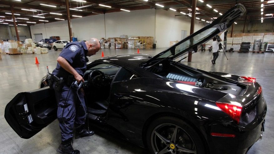 "U.S. Customs and Border Protection (CBP) officer Paulo Zanetti holds a fiber optic camera used to check the interior of gas tanks, next to a 2010 Ferrari 458 Italia ""supercar,"" one of  20 high-end stolen vehicles that were intercepted on their way to Honk Kong and Vietnam,  in Carson, Calif., on Tuesday, April 3, 2012. (AP Photo/Damian Dovarganes)"