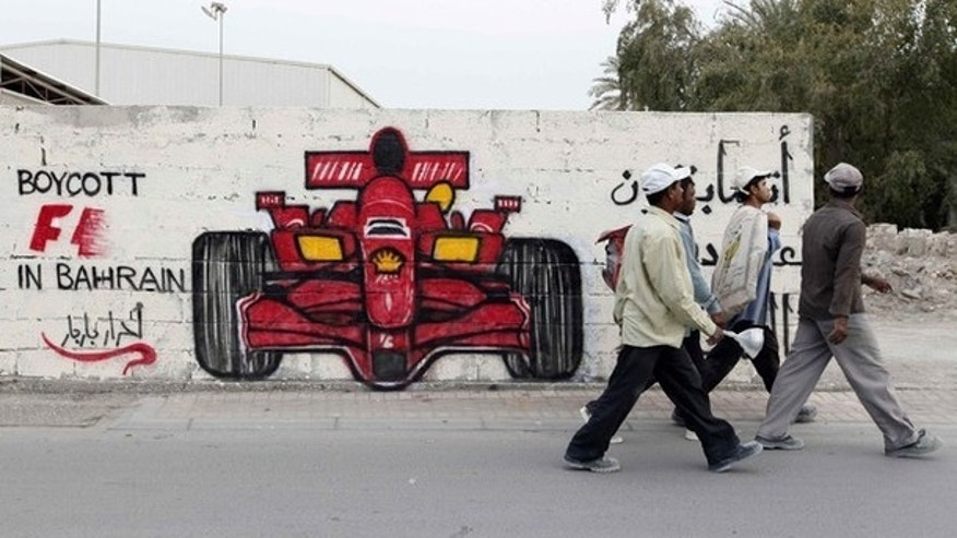 Men walk past anti-Formula One graffiti in the village of Barbar, west of Manama April 5, 2012. Former world champion Damon Hill has called on Formula 1 bosses to reconsider going ahead with this month's controversial Bahrain Grand Prix and warned that the sport's image could suffer if the race is held.