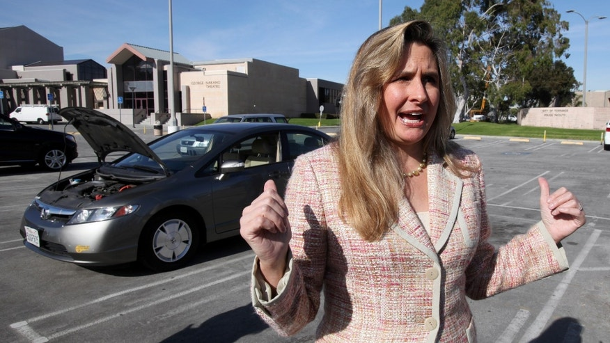 FILE - In this Jan. 3, 2012 file phtoo, Heather Peters, who says her 2006 Honda Civic Hybrid, rear, never achieved the 50 mpg Honda claimed in its advertising, talks with reporters outside small claims court in Torrrance, Calif. Honda appealed the $9,867 award to Peters who sued the giant automaker. She sued individually to avoid being part of a class action that promised participants only $200 each in a settlement with Honda. (AP Photo/Reed Saxon, File)