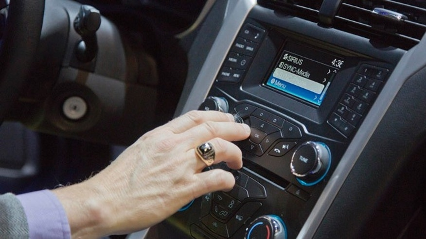 An industry affiliate tests out Ford's SYNC connection and entertainment system inside a Ford Fusion at the Consumer Electronics Show, Wednesday, Jan. 9, 2013, in Las Vegas. Ford's SYNC connects the car stereo and navigation system to a user's mobile device. (AP Photo/Julie Jacobson)