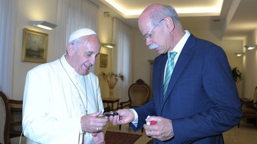 Pope Francis handed the keys to the Popemobile by Daimler CEO Dr. Dieter Zetsche.