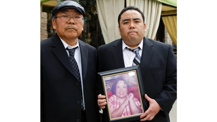 "FILE - This Thursday, Feb. 4, 2010 file photo shows Jeffrey Uno, right, and his father, Peter Uno, the son and husband of Noriko Uno, in framed photo, who died in an alleged ""sudden unintended acceleration"" crash in a Toyota Camry in August 2009, in Los Angeles. A jury on Thursday Oct. 10, 2013 found Toyota not liable for death of Noriko Uno.  (AP Photo/Damian Dovarganes, File)"