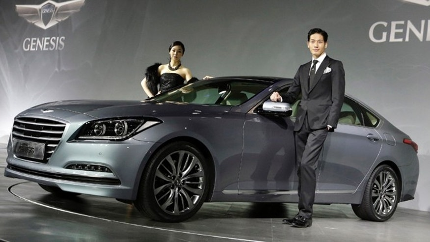 Models pose with Hyundai Motors' Genesis sedan for a press unveiling in Seoul, South Korea, Tuesday, Nov. 26, 2013. Hyundai has revamped the luxury Genesis sedan for the first time since 2008, attempting to elevate its brand and grab a bigger share of U.S. car sales as competition from American and European automakers erodes Hyundai's dominance in its South Korean stronghold. (AP Photo/Lee Jin-man)