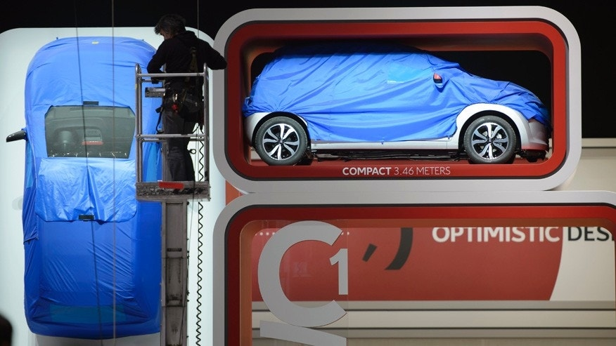 An employee   works  during the last preparations at the Citroen booth,  prior to the opening of the press preview days at the 84. Geneva International Motor Show in Geneva, Switzerland, Sunday, March 2, 2014.  (AP Photo/Keystone,Martial Trezzini)