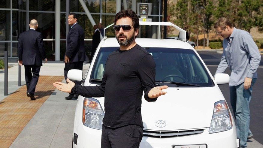 "FILE - In this Sept. 25, 2012 file photo, Google co-founder Sergey Brin gestures after riding in a driverless car with California Gov. Edmund G Brown Jr., left, and state Senator Alex Padilla, second from left, to a bill signing for driverless cars at Google headquarters in Mountain View, Calif. The California Department of Motor Vehicles on Tuesday, March 11, 2014, held a public hearing to solicit ideas on how to integrate driverless cars, sometimes called ""autonomous vehicles,"" onto public roads. (AP Photo/Eric Risberg, File)"