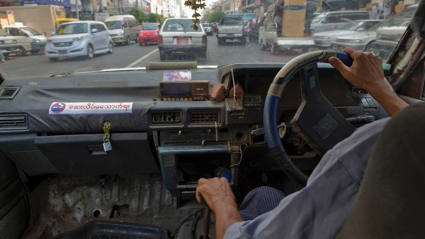 In this April 7, 2014 photo, a taxi driver navigates a 1989 Nissan Trad Sunny, one of few remaining clunkers, through traffic in Yangon, Myanmar. One of the quaintest of many anachronisms in Yangon, a city of moldering colonial villas and gleaming golden pagodas, used to be the decades old Toyotas, Chevys and other clunkers wheezing down its mostly empty roads, a visible sign of sanctions and economic isolation. Now, the streets have filled with a flood of newer used cars, mostly from Japan. (AP Photo/Gemunu Amarasinghe)