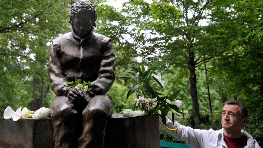 A man lays flowers next to a statue of Ayrton Senna, in a park close to the Imola track, Italy, Wednesday, April 30, 2014. It is a testament to Ayrton Senna's lasting impact on Formula One that the 20th anniversary of his death will be observed this week with five days of commemorations at the Imola track where he had his fatal accident. Current and past F1 drivers, mechanics, racing officials and fans will pay their respects to Senna and Austrian driver Roland Ratzenberger, who also died at the 1994 San Marino Grand Prix. (AP Photo/Marco Vasini)