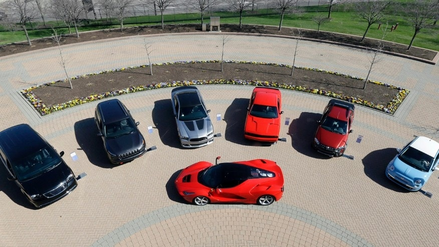 A LaFerrari, center, is displayed alongside Fiat and Chrysler vehicles at Chrysler Group LLC world headquarters in Auburn Hills, Mich., Tuesday, May 6, 2014. Fiat Chrysler Automobiles NV unveiled its business strategy for the next five years to investors as it prepares for life as a newly merged company. (AP Photo/Carlos Osorio)