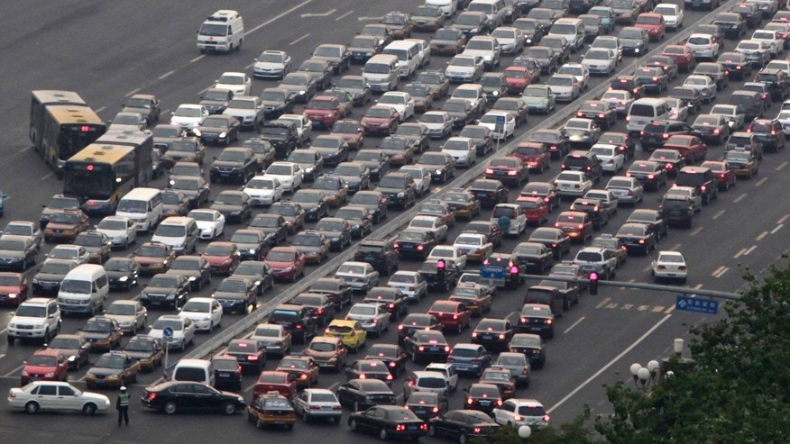 In this photo taken Monday, April 25, 2011, cars clog a main thoroughfare in Beijing, China. China's government plans to take 5 million older, polluting vehicles off the road this year in an effort to revive stalled progress toward cleaning up smog-choked cities. The plan also calls for filling stations in Beijing, Shanghai and other major urban areas to switch to selling only the cleanest grades of gasoline and diesel, according to a Cabinet statement issued Monday, May 26, 2014. (AP Photo/Ng Han Guan)