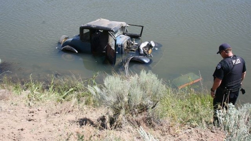 This photo provided by Oregon State Police, a 1930 Ford Model A coupe is submerged in the Crooked River south of Prineville, Ore., on Sunday, June 22, 2014.  Central Oregon authorities say a 79-year-old man took his 1930 Ford Model A coupe to church on Sunday to show it off. When he left it to get lunch, sheriff's deputies say it was stolen and crashed into the Crooked River.  Capt. Michael Boyd said 34-year-old Erik Blake Halpin, described as a transient, was arrested for investigation of drunken driving and unauthorized use of a vehicle. He swam to shore and was arrested after he was treated at a Bend hospital. (AP Photo/Oregon State Police)