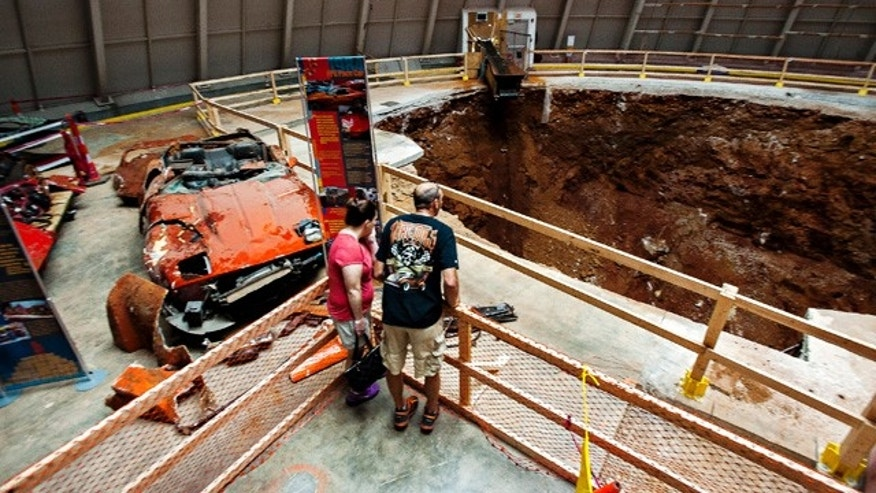 August 30, 2014: Kimberly, left, and David Tompkins lean over to take a look at the sinkhole during a visit at the National Corvette Museum in Bowling Green, Ky. (AP Photo/The Daily News, Miranda Pederson)