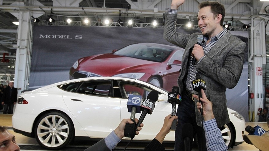 FILE - In this June 22, 2012 file photo, Tesla CEO Elon Musk waves during a rally at the Tesla factory in Fremont, Calif. Musk has five states bidding up subsidy packages to land a coveted plant for a $5 billion factory to make batteries for a new generation of Tesla electric cars. (AP Photo/Paul Sakuma, File)