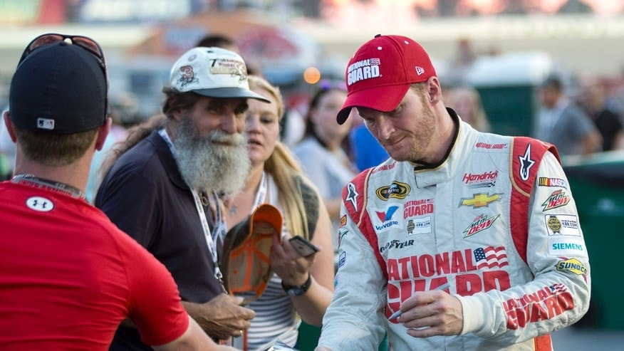 Sprint Cup Series driver Dale Earnhardt Jr. signs autographs after qualifying for Sunday's Oral B USA 500 NASCAR auto race at Atlanta Motor Speedway Friday, Aug. 29, 2014, in Hampton, Ga. (AP Photo/John Bazemore)