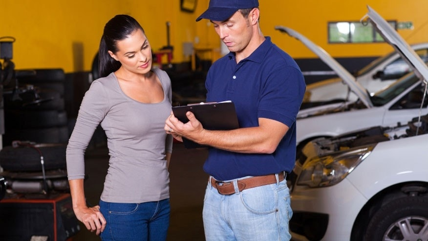 auto mechanic and young woman in workshop