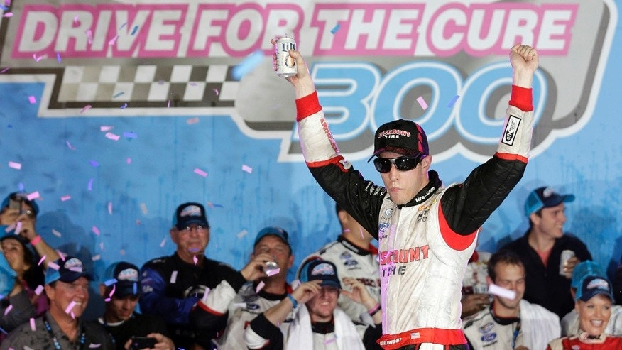 Brad Keselowski celebrates in Victory Lane after winning the NASCAR Nationwide series Drive for the Cure 300 auto race at Charlotte Motor Speedway in Concord, N.C., Friday, Oct. 10, 2014. (AP Photo/Chuck Burton)