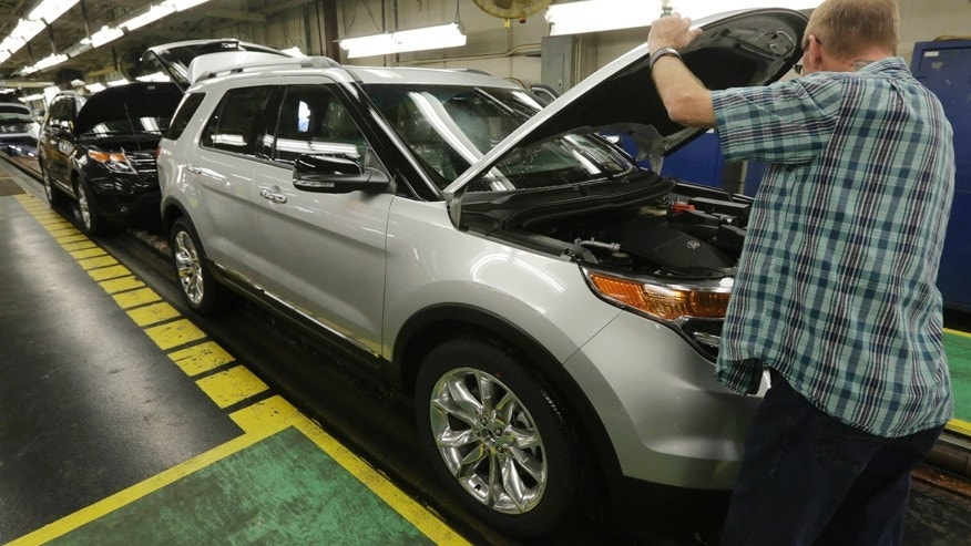 CORRECTS YEAR - In this Oct. 22, 2014 photo, workers perform final inspections on 2015 Ford Explorers on the assembly line at the Chicago Ford Assembly Plant. The seven-passenger Ford Explorer, introduced in the 1991 model year, was the first SUV that was equally at home navigating mountain trails or grocery store parking lots, says Karl Brauer, a senior analyst with the car buying site Kelley Blue Book. (AP Photo/M. Spencer Green))