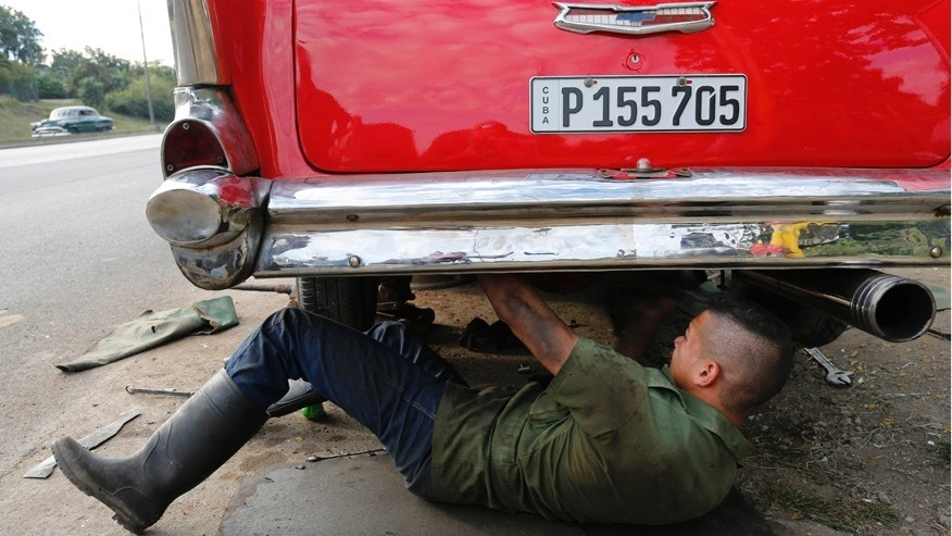 In this Dec. 19, 2014 photo, a mechanic works under a vintage American car in Havana, Cuba.  U.S. car sales have been banned in Cuba since 1959. Cubans have been have been forced to patch together Fords, Chevrolets and Chryslers that date back to before Fidel Castro's revolution which can make it appear like the country is stuck in a 1950s time warp. Since the Communist economic system isn't likely to change soon, many of those cars will have to stay on the road for years. (AP Photo/Desmond Boylan)