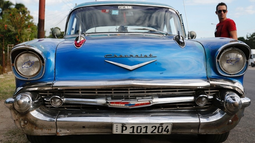 In this Dec. 19, 2014 photo, a man stands beside his 1957 Chevrolet Bel-Air car in Havana, Cuba.  U.S. car sales have been banned in Cuba since 1959. Cubans have been have been forced to patch together Fords, Chevrolets and Chryslers that date back to before Fidel Castro's revolution which can make it appear like the country is stuck in a 1950s time warp. Since the Communist economic system isn't likely to change soon, many of those cars will have to stay on the road for years. (AP Photo/Desmond Boylan)