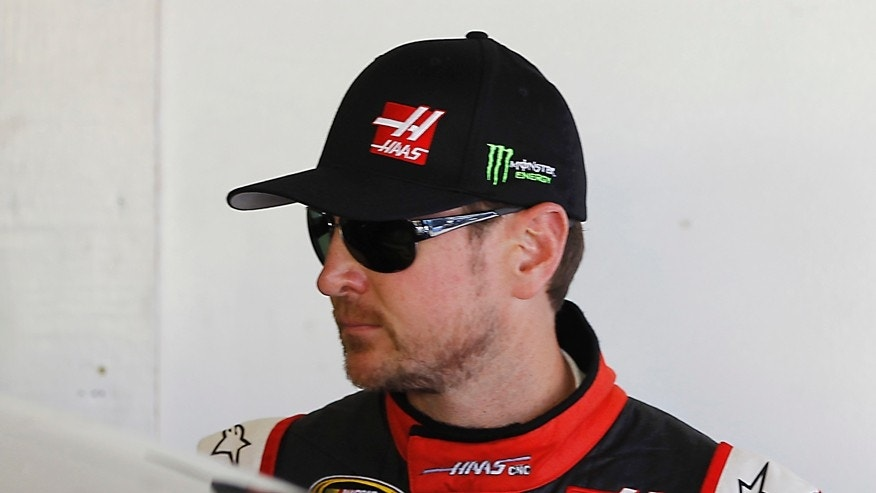 "In this Wednesday, Feb. 18, 2015 photo, Kurt Busch stands in his garage during a practice session for the Daytona 500 NASCAR Sprint Cup Series auto race at Daytona International Speedway, in Daytona Beach, Fla. In a stunning move just two days before the season-opening Daytona 500, NASCAR suspended Busch indefinitely on Friday, Feb. 20, after a judge said the former champion almost surely strangled and beat an ex-girlfriend last fall and there was a ""substantial likelihood"" of more domestic violence from him in the future. (AP Photo/Terry Renna)"