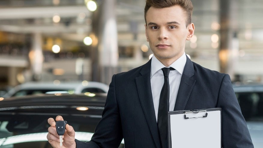 Here is your key! Confident young classic car salesman standing at the dealership and holding a key