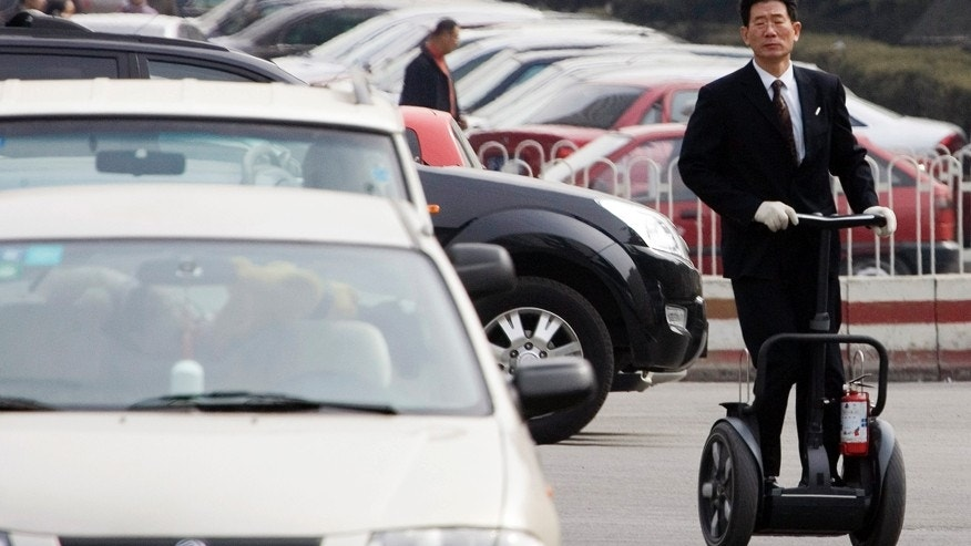 FILE - In this March 8, 2006 file photo, a Chinese man rolls on a Segway during his practice at a parking lot of a club where he sells the personal transporter in Beijing. Segway, the iconic but struggling U.S. maker of personal electric scooters, has been bought by a Chinese company. Beijing-based Ninebot Inc., which makes a range of short-distance motorized transport devices, said Wednesday, April 15, 2015 that it bought Segway for an undisclosed amount. Ninebot's purchase of New Hampshire-based Segway is the latest example of a Chinese company acquiring foreign brands or technology. (AP Photo/Ng Han Guan, File)