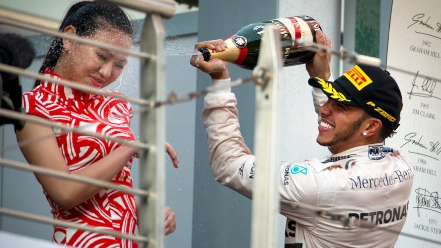 Mercedes driver Lewis Hamilton of Britain sprays champagne on a track attendant on the podium after winning the Chinese Formula One Grand Prix at Shanghai International Circuit in Shanghai, China, Sunday, April 12, 2015. (AP Photo/Mark Schiefelbein)