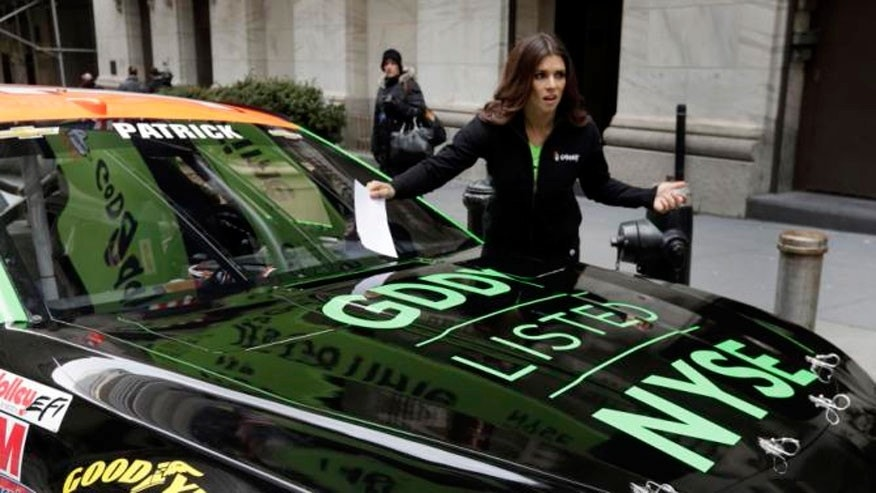 Race car driver Danica Patrick pretends to have received a parking ticket on her car in front of the New York Stock Exchange, before the GoDaddy IPO, Wednesday, April 1, 2015. (AP Photo/Richard Drew)