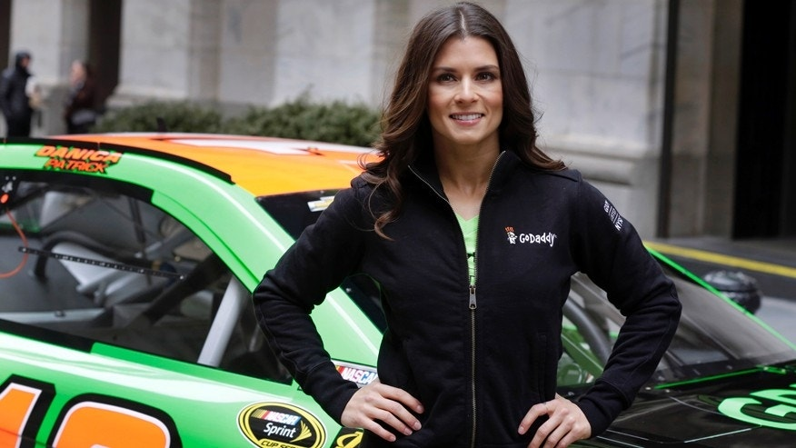 Race car driver Danica Patrick poses with her car in front of the New York Stock Exchange, before the GoDaddy IPO, Wednesday, April 1, 2015. (AP Photo/Richard Drew)