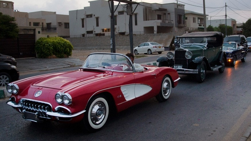 In this photo taken May 10, 2015, people drive their classic cars, on a street in Karachi, Pakistan. For an elite but passionate group of vintage car collectors in Pakistan, restoring antique rides is like traveling back in time and money seems to be no obstacle when the prize is a Lincoln convertible that belonged to an Afghan king or a Rolls-Royce once used by Indias last viceroy. (AP Photo/Shakil Adil)