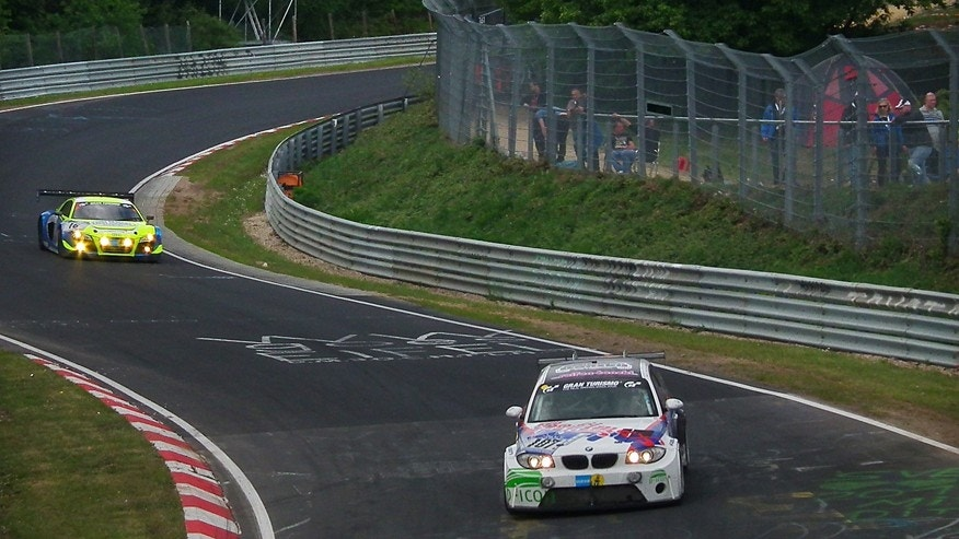 In this Saturday, May 16, 2015 photo, cars compete at speeds around 200 kilometers (120 miles) per hour in a 24-hour endurance race at Nuerburgring in the Eifel Mountains in Germany. Over 500 drivers and some 160 cars entered the race but only half of them crossed the finish line, in a show of determination.. (AP Photo Maciej Sakowicz)