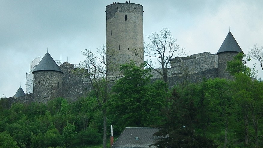 In this Saturday, May 16, 2015 photo, people are seen atop the tower of a medieval castle in Nuerburg, Germany appreciating the panorama of the wooded area that includes the Nuerburgring car-racing track. Race drivers call it The Green Hell and it has taken dozens of drivers lives, but Germanys Nuerburgring car-racing track offers unparalleled excitement for car racing fans. (AP Photo/Maciej Sakowicz)