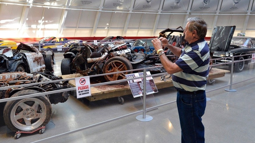 In this Wednesday, Aug. 12, 2015, photo, Terry Jorgensen of Deland, Fla., takes a photo of the cars that were swallowed by the sinkhole at the National Corvette Museum in Bowling Green, Ky. The hole has been fixed but not forgotten at the museum. Yellow tape now marks the boundaries of the cavity that became a sensation and put the museum on the map. (AP Photo/Timothy D. Easley)