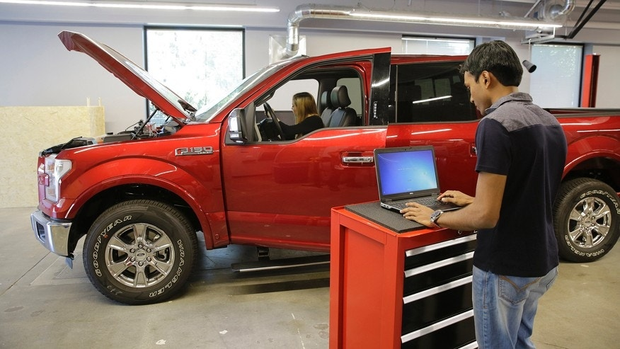 In this photo taken Thursday, Aug. 13, 2015, Nitin Bandaru, right, works on a hackathon project at the Ford Motor Company Research and Innovation Center in Palo Alto, Calif. The convergence of cars and technology is blurring the traditional geographical boundaries of both industries. Silicon Valley is dotted with research labs opened by automakers and suppliers, who are racing to develop high-tech infotainment systems and autonomous cars. (AP Photo/Eric Risberg)
