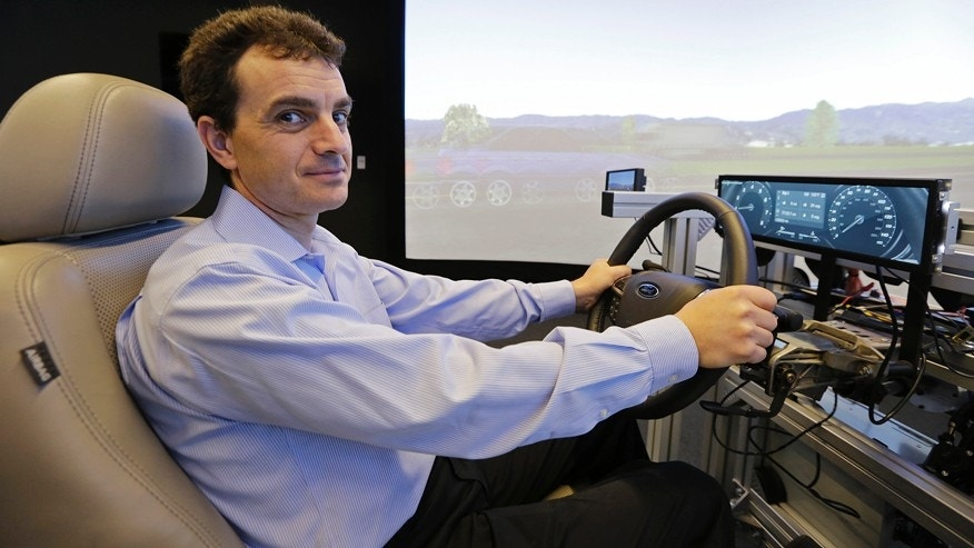 In this photo taken Thursday, Aug. 13, 2015, technical director Dragos Maciuca poses while sitting in a driving simulator in the immersion lab of the Ford Motor Company Research and Innovation Center in Palo Alto, Calif. Maciuca left Apple this year to become the technical director of Fords Silicon Valley lab. Maciuca, an engineer who worked for BMW and Nissan in the late 1990s, says auto companies got little respect in Silicon Valley until a few years ago. But that changed after automakers moved in and started helping tech firms understand how to incorporate their apps and software into cars. (AP Photo/Eric Risberg)