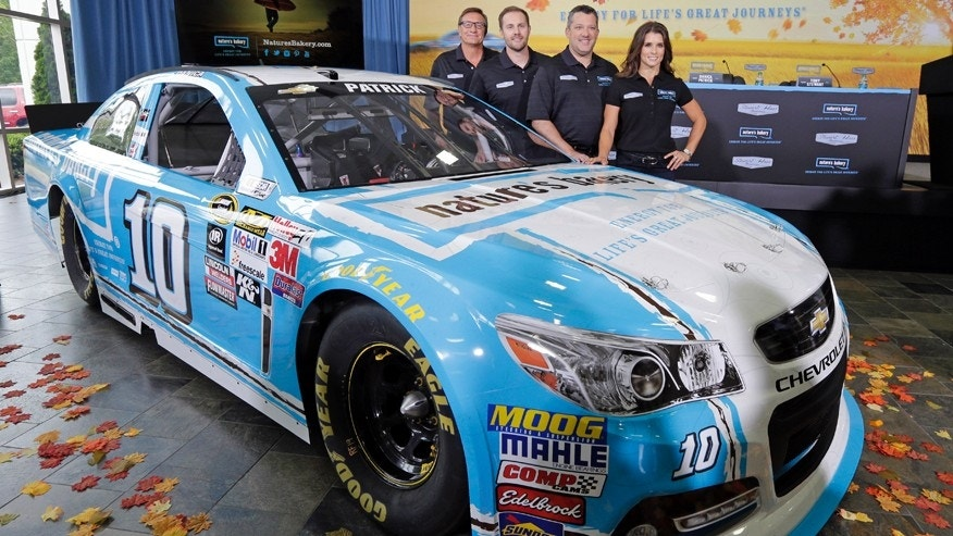 From right, Danica Patrick, Tony Stewart, Sam Marson, and Dave Marson, pose by Patrick's race car during a news conference to announce a new sponsorship for her NASCAR auto racing team at Stewart-Haas Racing's headquarters in Kannapolis, N.C., Tuesday, Aug. 18, 2015. (AP Photo/Chuck Burton)