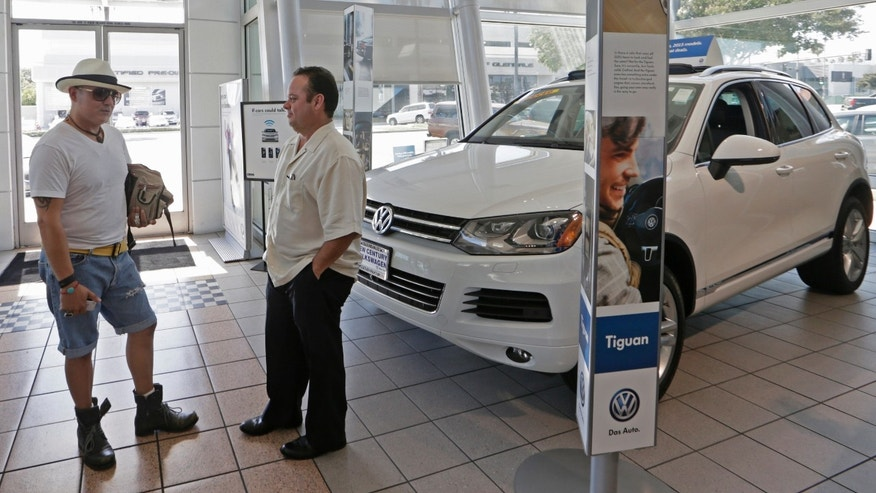 In this Thursday, July 2, 2015, photo, customer Armando Barillas, originally from Guatemala, left, talks to Sergio Rosas, sales manager at the New Century Volkswagen dealership in Glendale, Calif. At least 31 models are being redesigned for 2016, including big names like the Volkswagen Passat and the Toyota Prius, according to the car buying site Edmunds.com. So, dealers are slashing thousands of dollars off the cost of 2015 models to clear them off their lots. (AP Photo/Damian Dovarganes)