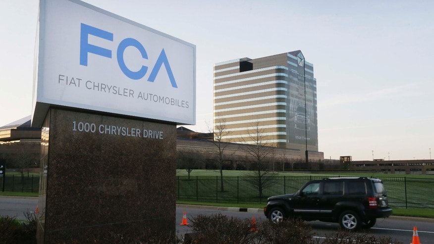 FILE - In this Tuesday, May 6, 2014, file photo, a vehicle moves past a sign outside Fiat Chrysler Automobiles world headquarters in Auburn Hills, Mich.
