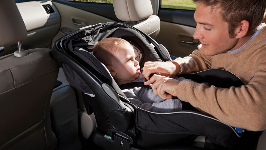 Father buckling baby into car seat
