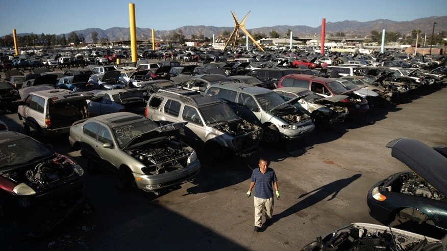 In this Wednesday, Nov. 11, 2015 photo, a customer walks through the yard of Aadlen Brothers Auto Wrecking, also known as U Pick Parts, in the Sun Valley section of Los Angeles. The junkyard is closing on New Year's Eve, and everything must go by then, the cars, the shark, the arches, even the giant car-crushing machine. (AP Photo/Jae C. Hong)