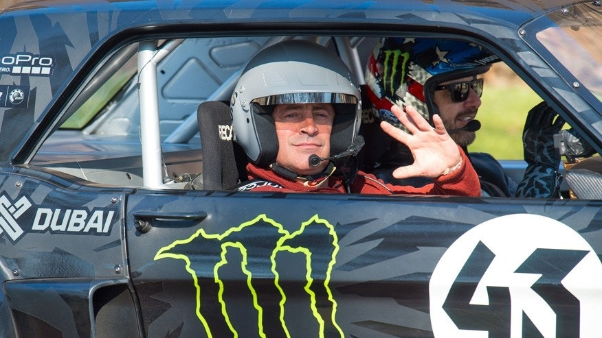 Actor and Top Gear presenter  Matt LeBlanc, left, waves , as he sits with  rally driver Ken Block during filming of BBC Top Gear in Westminster, London on Sunday Sunday March 13, 2016.