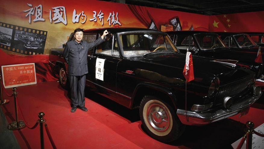 In this Sunday, March 27, 2016, photo, Luo Wenyou poses by his Red Flag car which he used in the 1998 vintage car rally to drive from the northeastern city of Dalian to Beijing, at his private museum in Huairou district of Beijing. As China grows richer, wealthy citizens, banks and private businesses have invested in Chinese art and started museums to display their wealth or patriotism. Others, such as Luo, opened their collections after their pastimes evolved into callings. (AP Photo/Andy Wong)
