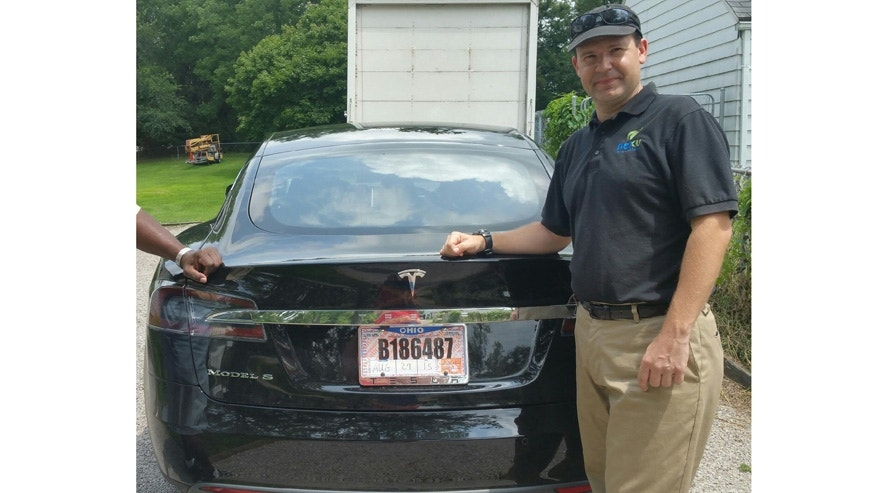 FILE - In this 2015 file photo provided by his neighbor, Krista Kitchen, Joshua Brown stands by his new Tesla electric car near his home in Canton, Ohio. (Krista Kitchen via AP, File)