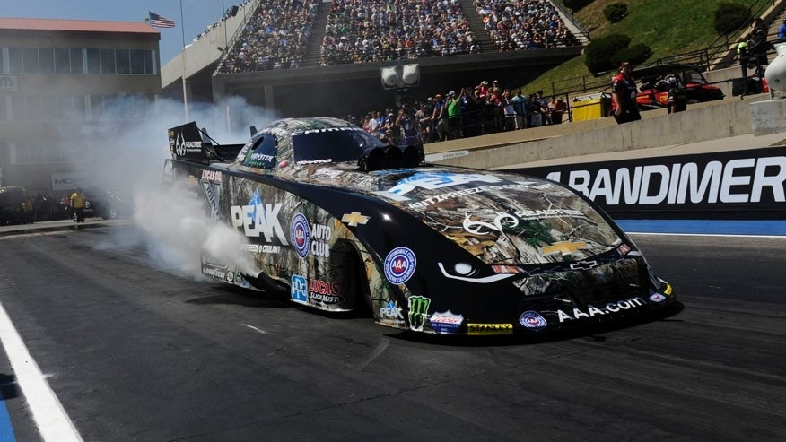 In this photo provided by NHRA, John Force prepares for a run in Funny Car during the Mopar Mile-High NHRA Nationals.