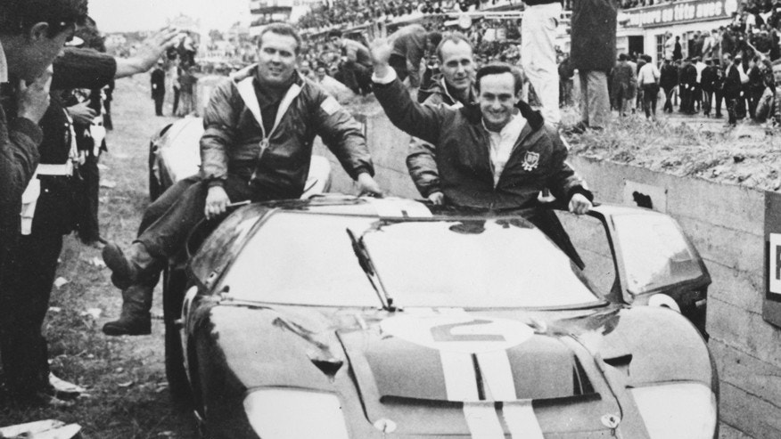 New Zealand's Chris Amon, right, waves to the crowd from his 7-litres Ford automobile after he and compatriot Bruce McLaren, not shown, won the 24-hours endurance for sports cars, at Le Mans, France, June 19, 1966. Two other bog Fords came in second and third to end Ferrari's six-year domination of the classic race. Celebrating with the driver are two unidentified members of the Ford team.  (AP Photo)