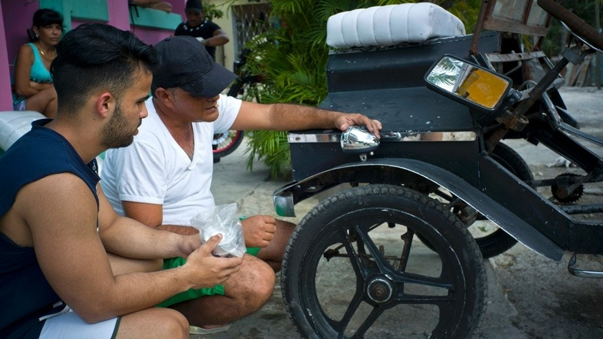 Dany Gomez, left, and his uncle Pavel, test lights on a homemade replica of a Model-T Ford, in Havana, Cuba, Tuesday,  Feb. 21, 2017. In a country where few can afford a car, a group of high school students have built a replica of a Model-T Ford with pedals instead of a gasoline engine, painstakingly acquiring and installing thousands of nuts, bolts and used car parts to complete their creation. (AP Photo/Ramon Espinosa)