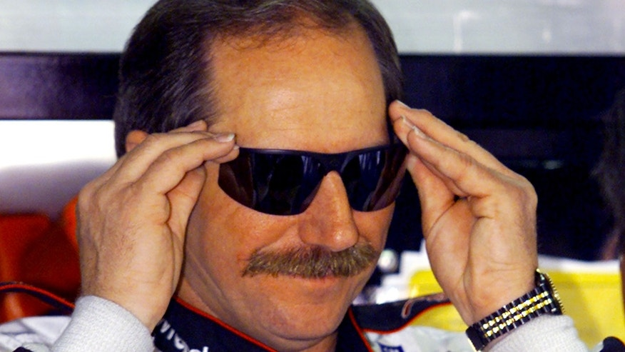 Late NASCAR driver Dale Earnhardt adjusts his glasses as he prepares to practice for the upcoming Daytona 500 at the Daytona International Speedway.
