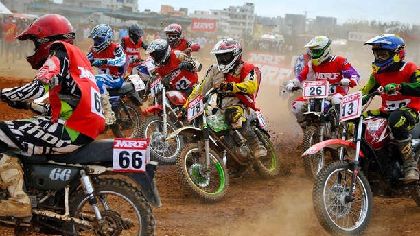 Riders turn a corner on their motorcycles during the National Supercross Championship in the southern Indian city of Bangalore November 30, 2014. More than 50 riders on Sunday took part in the national-level motorcycle championship. REUTERS/Abhishek N. Chinnappa (INDIA - Tags: SPORT MOTORSPORT) - RTR4G45G